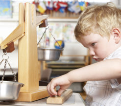 young boy weighing his toys